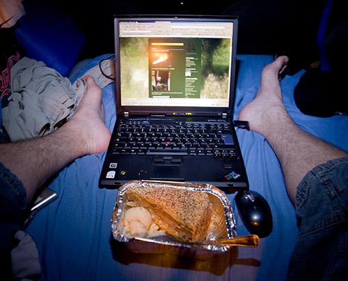 Füße, Laptop und Kuchen mit Vanilleeis