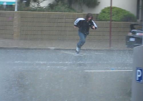 Durch den Regen rennendes Maedchen